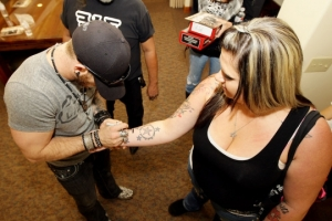 A fan gets Brantley Gilberts autograph for her tattoo